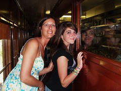 my dauhgter and granddaughter looking through the window into the kitchen area of the wine train
