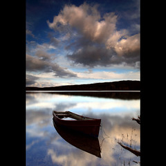 Boat - Kennard Loch (angus clyne) Tags: life wood uk travel blue light red sky cloud lake storm black mountains cold reflection tree green art love home water rain yellow forest canon dark landscape photography hope gold evening scotland boat moving spring highlands high fishing pond