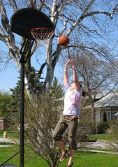 jump shot! (ailie*) Tags: street blue trees light sky house motion net girl grass basketball sport ball fun person spring jump jumping warm shot bright action branches sunny midair ailie