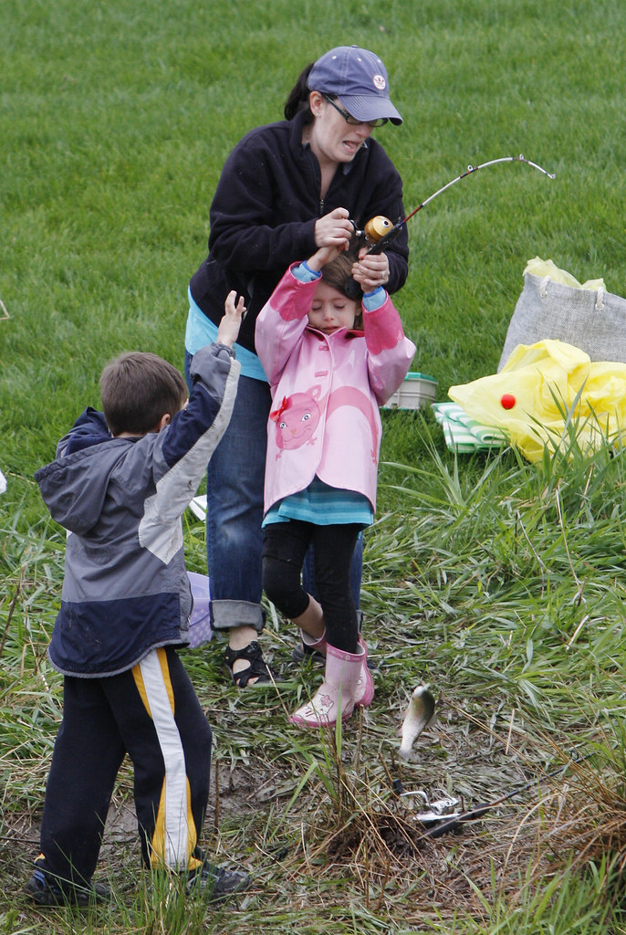 May 8, 2010 - Cristina Fox from Florence helps her daughter Gabriella Fox, 6, reel in a fish at the Family Fishing Event hosted by The U.S Fish and Wildlife Service in Hadley. Trevor Maslowski, 6, from Leeds cheers them on as they bring it in.