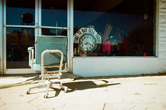Time to Buy (shiphome) Tags: autumn clock 35mm chair americana thesouth nikonfm2 smalltown newtoncounty warmsunshine lomography100 watertowerreflection mansfieldga teamshipaway timeanddistance technicolorsouth firstsaturdayinnovember