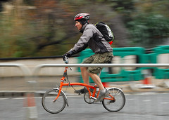 A hardy soul (jeremyhughes) Tags: city winter urban orange motion blur london bike bicycle speed movement nikon cyclist zoom shorts streetfurniture nikkor panning barriers folder vr folding cannonstreet foldingbike brompton 18200mm d40 brommo foldie