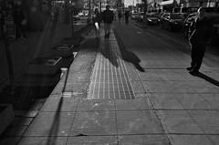 Stand (sniderscion) Tags: street light shadow people urban bw white toronto ontario canada black reflection silhouette metal dark scott walking grate nikon shiny downtown glare traffic bright candid canadian grill sidewalk busy flare pedestrians tamron sunbeam f28 snider d80 1750mm tamronspaf1750mmf28 flickrgolfclub sniderscion clanflickr