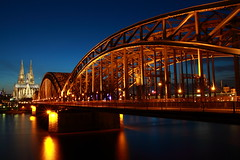 Hohenzollern Bridge, Kln, Germany (Mihai Andritoiu) Tags: city longexposure bridge blue light urban reflection monument water station architecture night river germany deutschland photography lights evening photo cityscape cathedral dusk dom tripod central cologne railway wideangle kln clear hauptbahnhof german hour transportation dome getty rhine rhein gettyimages klnerdom starbursts klner hohenzollern canon500d hohenzollernbrcke vle 5photosaday canoneos500d sigmaafos182003563dc t1i outstandingromanianphotographers