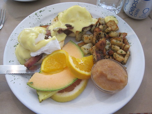 Eggs benedict, potatoes, fruits, apple sauce