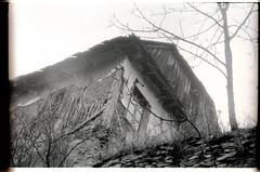 Rainy day. Kalotaszeg, Romania, 1992 (krokodil.nana) Tags: old bw film rain village romania overexposed grainy transylvania crumbling mudwall