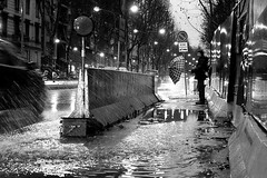 description of a urban shower (Donato Buccella / sibemolle) Tags: street blackandwhite bw italy milan rain umbrella milano streetphotography puddles moscova canon400d sibemolle ipedonimaltrattatidagliautomobilisti ur