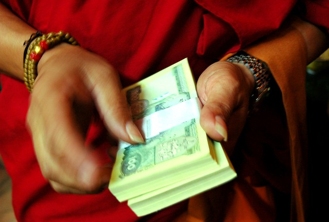 Tibetan Buddhist monk in red robes handing out money in 100 ruppee notes, the donations, to individual lamas, monks and nuns, Tharlam Monastery, Kathmandu, Nepal