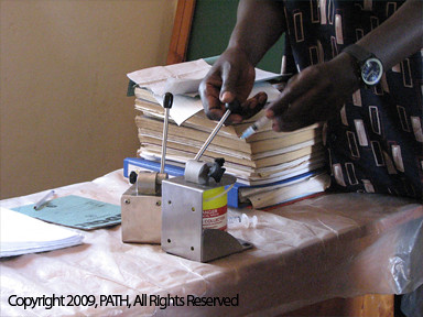 Health worker using a needle remover in Uganda