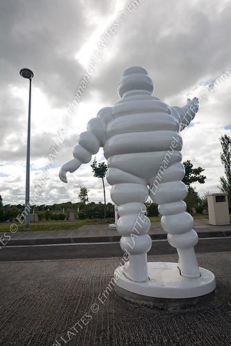 Sculpture en résine du Bibendum Michelin, de dos, sur une aire a