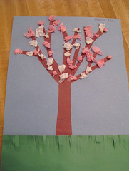 Construction paper tree filled with white and pink (tissue paper) blossoms, by Speck