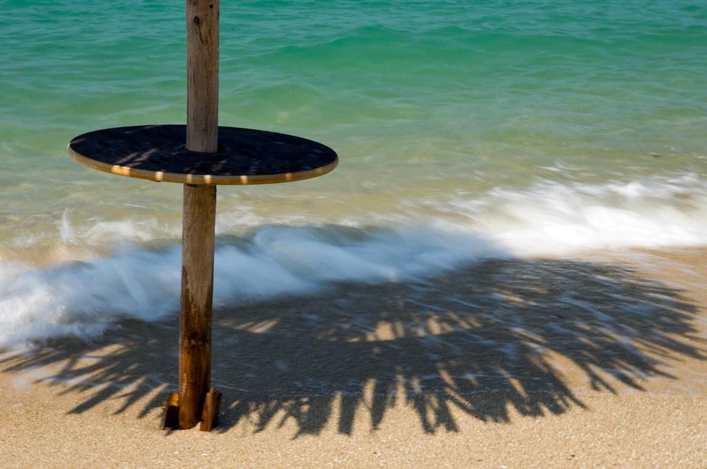 Wooden table around beach umbrella