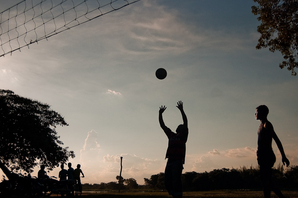 Lugareños de Puerto La Niña juegan partidos de volley en la tarde del viernes santo, bajo un arbol de lapacho, a metros del Río Jejuí. (San Pedro, Paraguay - Elton Núñez)