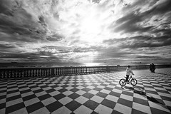 Biker (Philipp Klinger Photography) Tags: italien light shadow sea sky people bw italy white playing black bike person kid nikon meer europa europe mediterranean italia mare pattern cyclist child play angle terrace geometry wide kind tiles cycle tuscany esplanade promenade boardwalk biker rays toscana philipp livorno sigma1224mm mediterraneansea chessboard toskana klinger mittelmeer leghorn d700 dcdead theboywasbikingsofastthaticouldntfollowhimwiththecamera thesuncameoutjustforafewsecondsincludingtheraysintheback