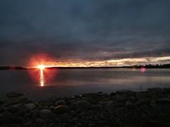 A glimpse of a sun (BigWhitePelican) Tags: sea sun clouds sunrise finland helsinki vanhankaupunginlahti rocks fujifilmfinepixhs10