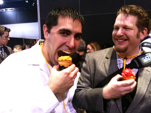 Justin Levy eats a cupcake at the Kodak Tweetup with Chris Brogan looking on