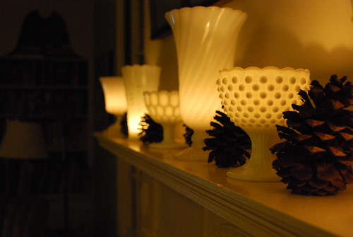 An idea to steal for sure. Line mantlepiece with white milk glass vases and place candles inside, via Flickr: SpiderWomanKnits