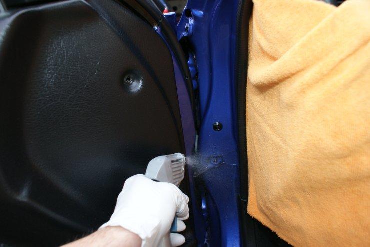 Spraying cleaner in door jamb