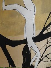 pintada mujer desnuda haciendo el pino en rama de árbol