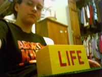 a girl with glasses sits behind a yellow block of legos where the word LIFE is written in red legos