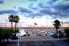 A cloudy and cool sunset (Fnikos) Tags: port puerto waterfront sea mar boat sailboat cloud sky skyline palmtree sidewalk vehicle outdoor