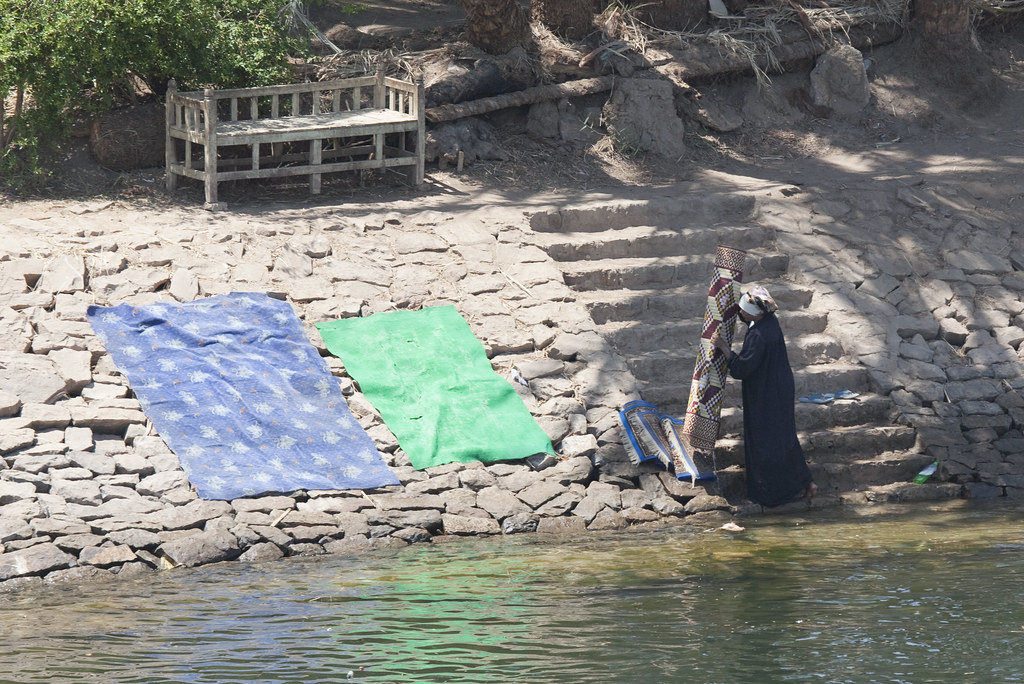 Woman washing carpets in the Nile