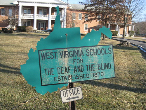 A sign shaped like West Virginia that reads: West Virginia Schools for the Deaf and Blind Established 1870