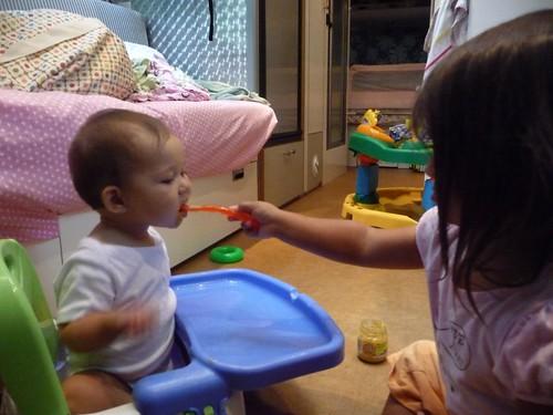 feeding her little sister.