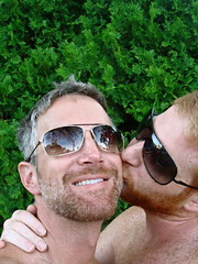 love in the bushes (redjoe) Tags: light hairy sun green love smile sunglasses tongue hair outside ginger washingtondc us dc backyard kiss afternoon hand cheek fuzzy redhead together facialhair freckles redhair shoulder bushes fuzz saltandpepper redjoe joehorvath