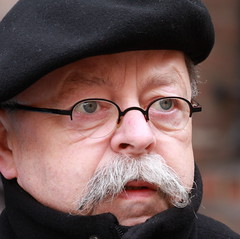 Ongerust (Plutone (NL)) Tags: portrait man glasses blauw denhaag moustache ogen portret zwart bril grijs binnenhof snor alpino baret