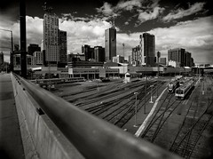rail intersection (mugley) Tags: city bridge sky urban blackandwhite bw 120 film lines skyline architecture modern clouds rollei buildings mediumformat prime 645 cityscape dof towers perspective tracks railway australia melbourne wideangle trains victoria scan negative convergence epson docklands railing polarizer 6x45 r3 mamiya645 urbanlandscape redfilter railyards polariser latrobest 25a v700 mamiya645protl bourkeplace m645 rolleir3 neo200 mondriane 35mmf35sekorn 120spencer atlantistower