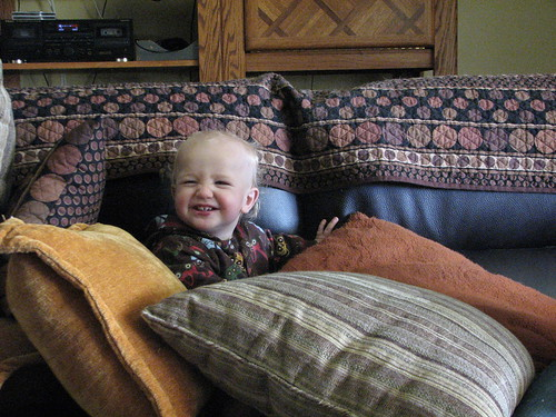 Baby smiling on a leather couch