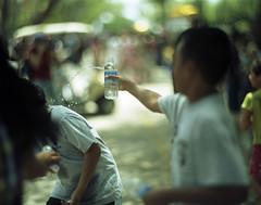 Splash (heart_of_au) Tags: color film water tampa bottle florida kodak thai 4x5 aquafina splash wat pour 160vc portra largeformat graflex decisivemoment songkran speedgraphic presscamera portra160vc 7inch vividcolor thaiculture douse aeroektar pacemakerspeedgraphic kodakaeroektar thaiamerican watmongkolrata