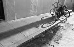 Through all I sit here and I wait (QsySue) Tags: blackandwhite slr bicycle concrete shadows bikes wideangle sidewalk 35mmfilm venicebeach canonae1program mudpuddle fomapan100 developedathome 28mm128 35mmfilmcamera titleisanelolyric