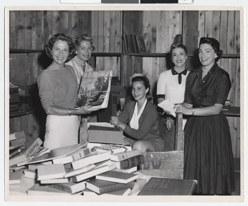 several women in a black and white photo standing around a table of books and smiling