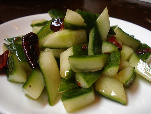 A dish of diagonally-cut skin-on cucumber pieces piled up on a small plate.  The pieces glisten with a light-coloured oil dressing, and pieces of dried red chilli are tucked in amongst them here and there.