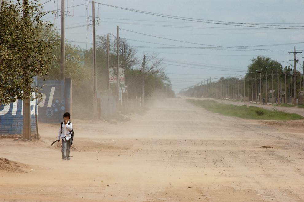 Un Niño camina hacia su Escuela por una de las calles de Loma Plata en un típico día de mucho viento y polvo (Elton Núñez - Loma Plata, Paraguay)