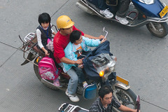 Man with helmet and two kids on a motorcycle in Yangshuo, Guilin