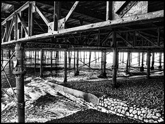 under the pier )bw (Paul Adames Noble) Tags: ocean old uk sea blackandwhite signs abandoned beach broken monochrome metal architecture contrast warning rust waves olympus pebbles erosion windswept southofengland rails walkways hastings seafront crisscross eastsussex hdr weatherd withoutatripod e520