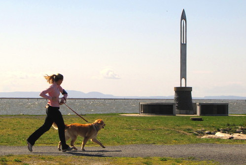 Girl and dog run pass Steveston Fisherman's Memorial at Garry Point Park