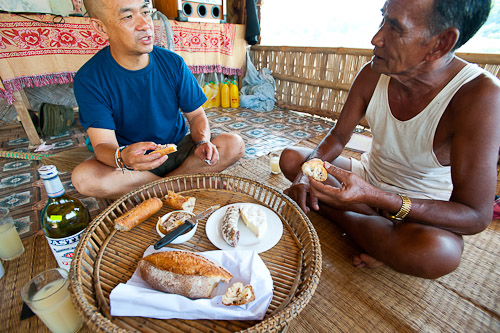 Christophe and local boatman enjoying French eats near the banks of the Nam Lik, Laos