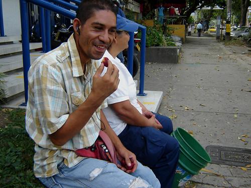 3:39 PM. El cuidador de carros de la cuadra, Francisco Javier, se acercó a saludar a la vendedora y recibió tres fresas de regalo. Entre pregón y pregón y durante unos quince minutos, hablaron del viento que soplaba y de lo caros que están los arrendamien