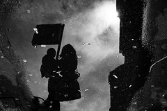 wet love (Donato Buccella / sibemolle) Tags: street blackandwhite bw italy milan reflections milano mm raining motherandson cadorna mg6748 sibemolle fotografiastradale daysrainpuddles