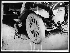 One of the lady ambulance drivers underneath her car attending to something that has gone wrong