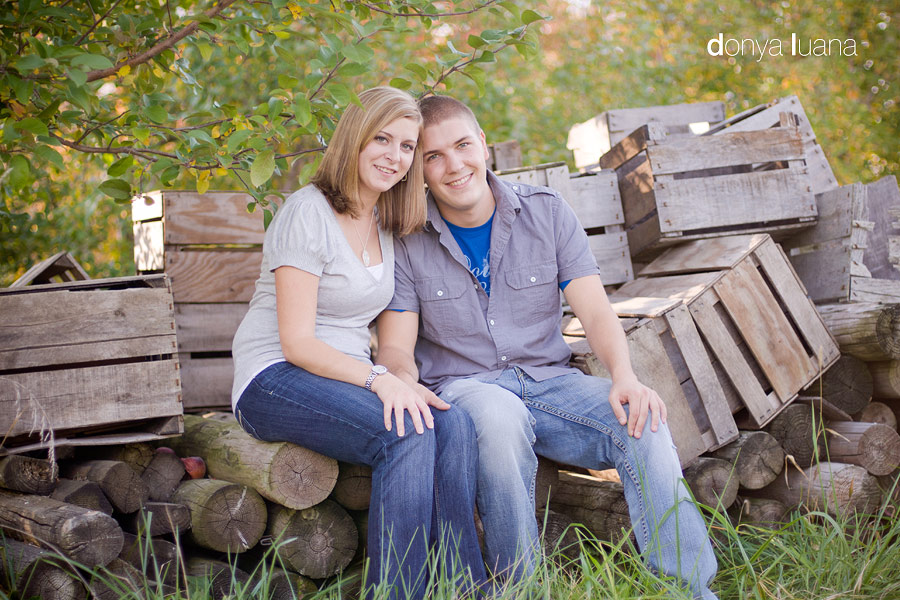 Northfield Couple poses at Apple Orchard near empty crates for Engagement Photography