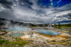 Yellowstone Skies Over Biscuit Basin (moerden68) Tags: yellowstonenationalpark montana wyoming hotspring caldera volcano water bacteria colors sonya7ii sonyilce7m2 manualfocus legacylens zeissdistagont15mmf28zf2 mountains clouds thunder sky forest wood pinetrees geysir platinumheartaward