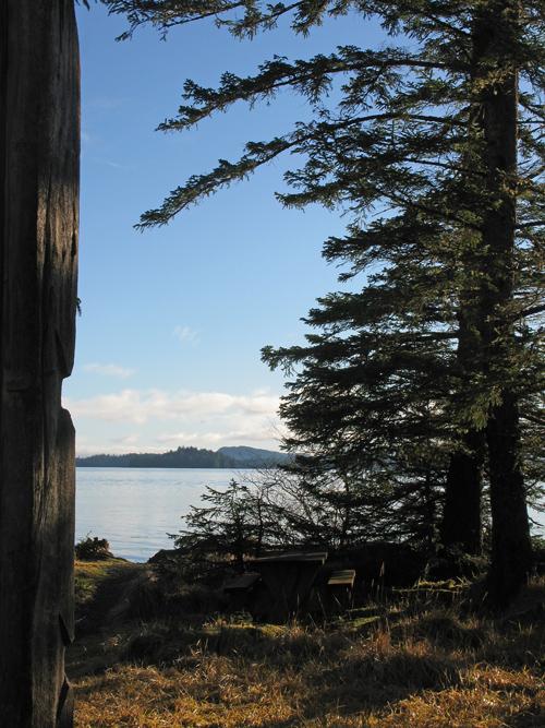 a view of Kasaan Bay between a totem and trees, Kasaan, Alaska
