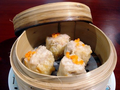 A bamboo steamer basket with the lid propped ajar and four siu mai dumplings sitting inside.  Each dumpling is topped with a few cubes of carrot.