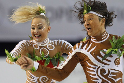 two white ice dancers in brown bodysuits with white swirls, white facepaint, and leaf decorations
