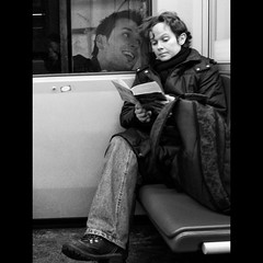 Funny reading (Sator Arepo) Tags: vienna leica urban blackandwhite bw smile car train reading austria book coach funny sitting boots metro pages coat streetphotography explore viena frontpage dlux dlux4 retofez120124